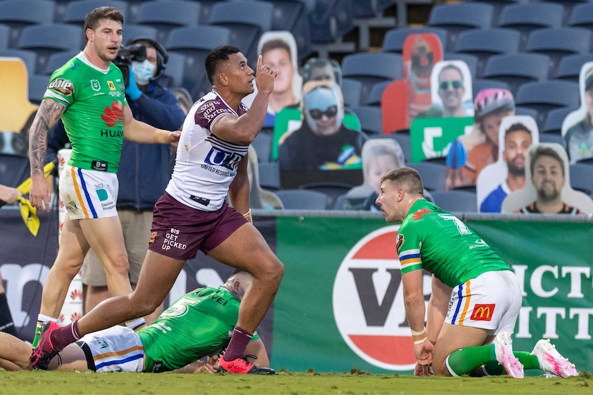 An NRL player looks up and points to the sky after scoring a try, as defenders lie on the ground.