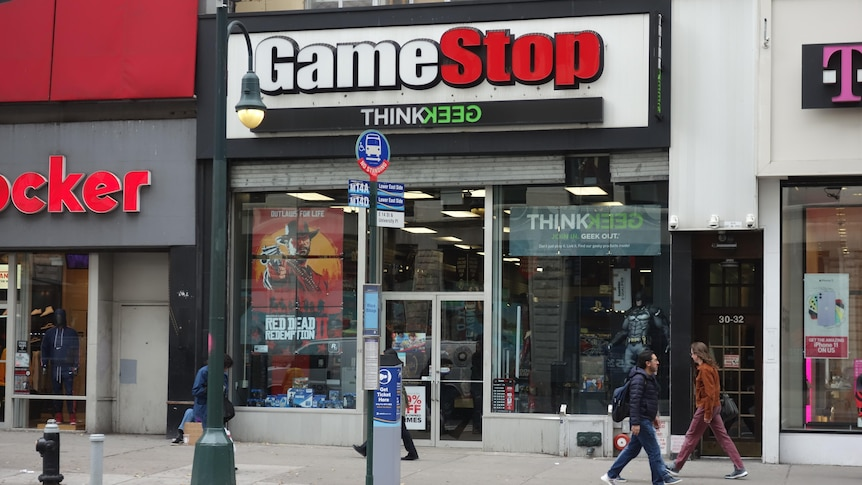 People walk past a GameStop store in Manhattan, New York, in a story about what to know before investing in GameStop GME.