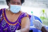 A Papua New Guinean woman in a face mask sits next to a nurse holding a needle