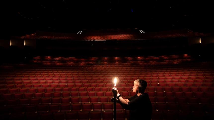 Sydney Opera House lighting chief Ange Sullivan lights a lonely globe in the empty auditorium