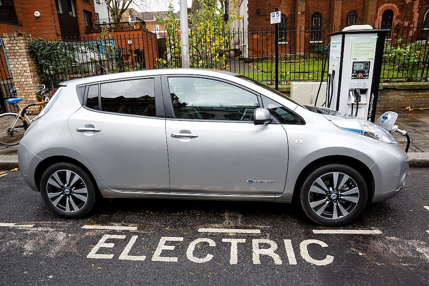 A silver electric car plugged in to charge.