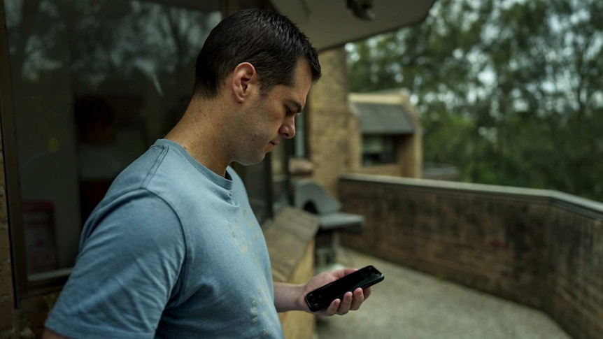 Man with black hair in blue t-shirt stands on balcony looking at phone in his hand with brick building and trees in background.