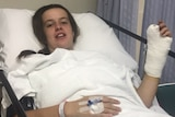 Britney Thomas in a hospital bed after surgery waving a hand in cast.
