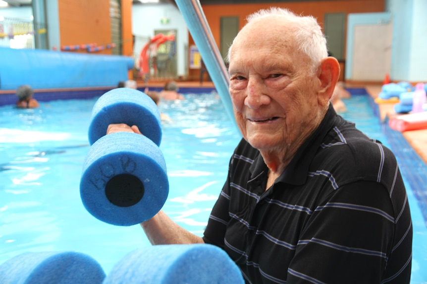 An elderly man grins at the camera as he lifts foam hand weights by the pool side.