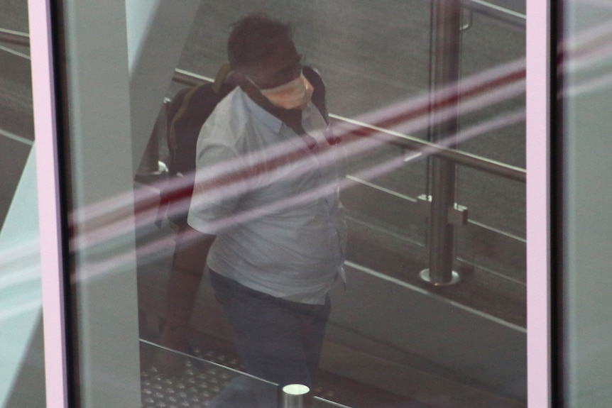 A man wearing a face mask and carrying a backpack walks in a corridor behind glass at Perth Airport.