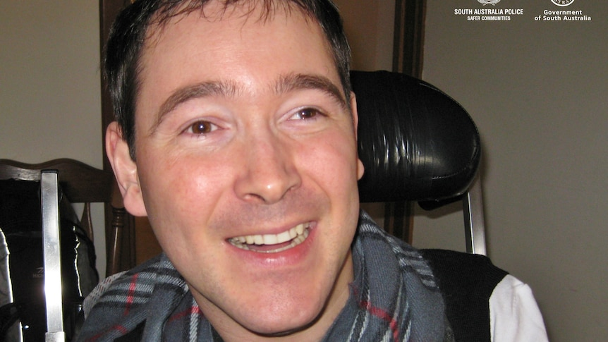 A man with dark hair wearing a grey checkered scarf smiles as he sits in a black wheelchair