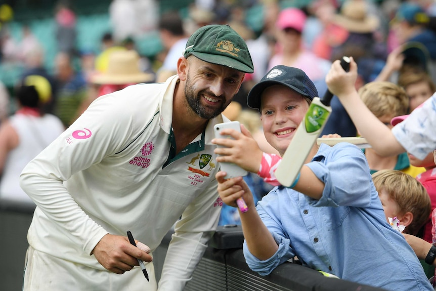A smiling Australian player stands next to a young cricket fan near the boundary after a Test.