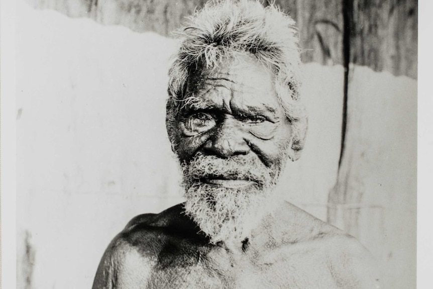 A mid-shotmonochrome portrait from World War 1 era of a man with a beard and no shirt.