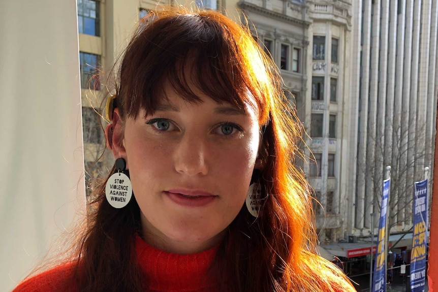 A young woman with a red jumper and earrings that read 'stop violence against women'.