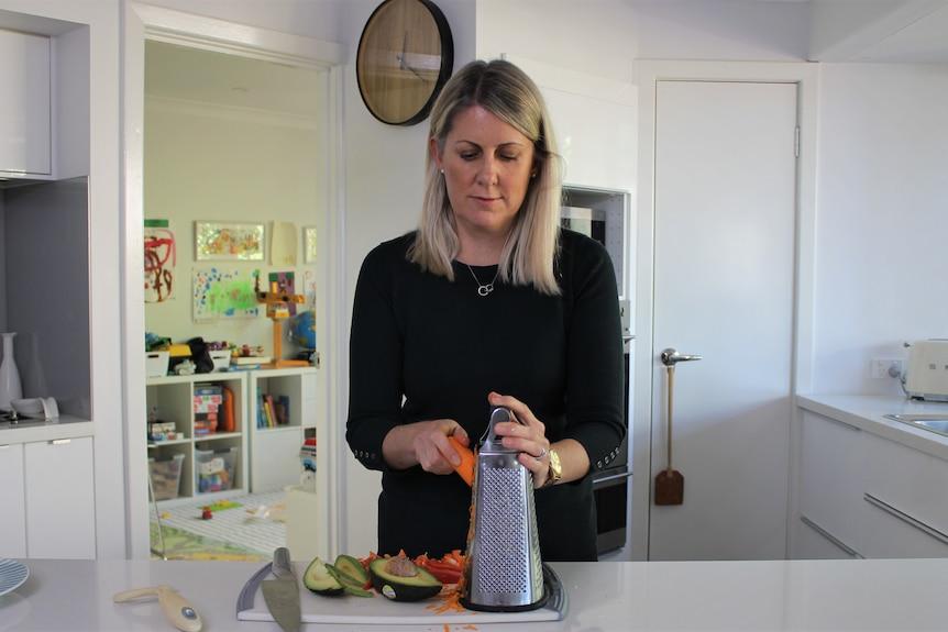 woman in kitchen shredding carrot