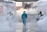 A person in a blue full body medical suit walks in a corridor flanked by two others spraying disinfectant in large white smoke.