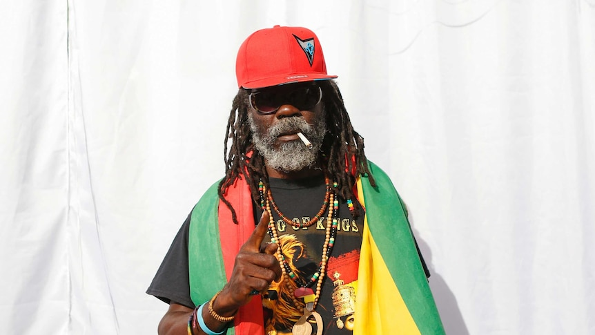 An elderly Rastafarian stands with a multicoloured flag around his neck.