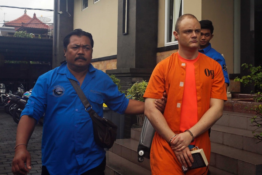 IsaacEmmanuelRoberts wears an orange jumpsuit and is escorted from a building in Bali.
