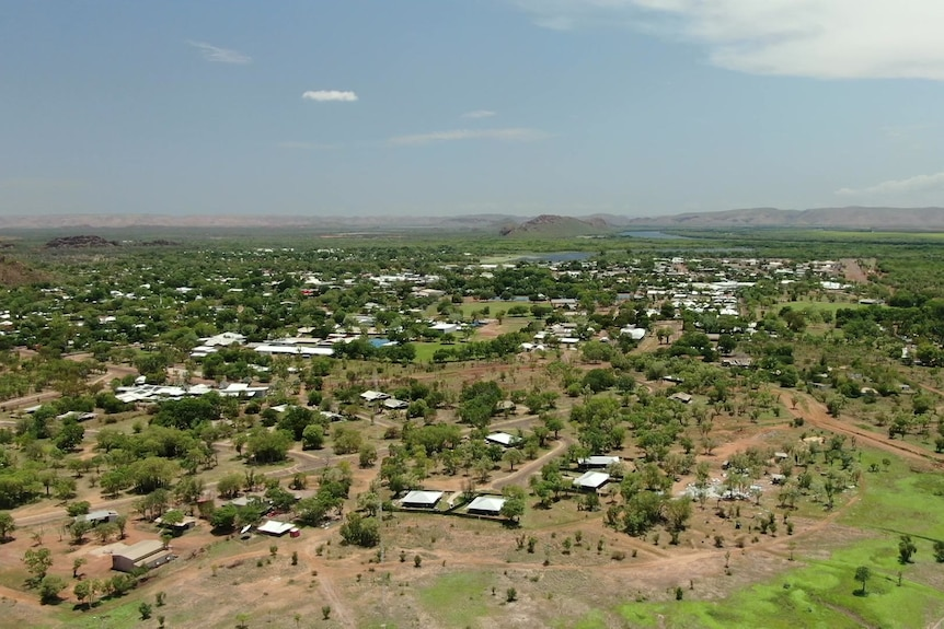 A drone shot above Kununurra, a green flat town, with hills in the far distance.