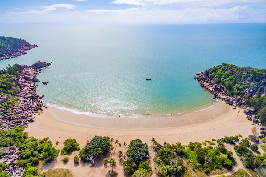 An aerial shot of a stunning beach fronting a sublime blue-green sea.