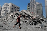 Man walks past the rubble of a destroyed building in Gaza