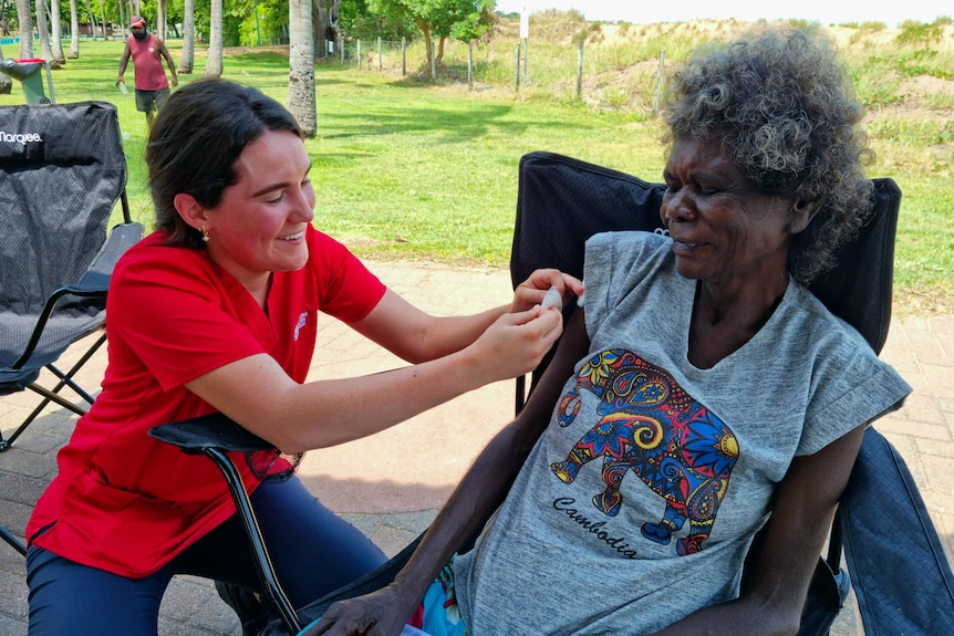 A woman applying a bandaid to another woman's arm after vaccinating her at a park, with greenery in the background.