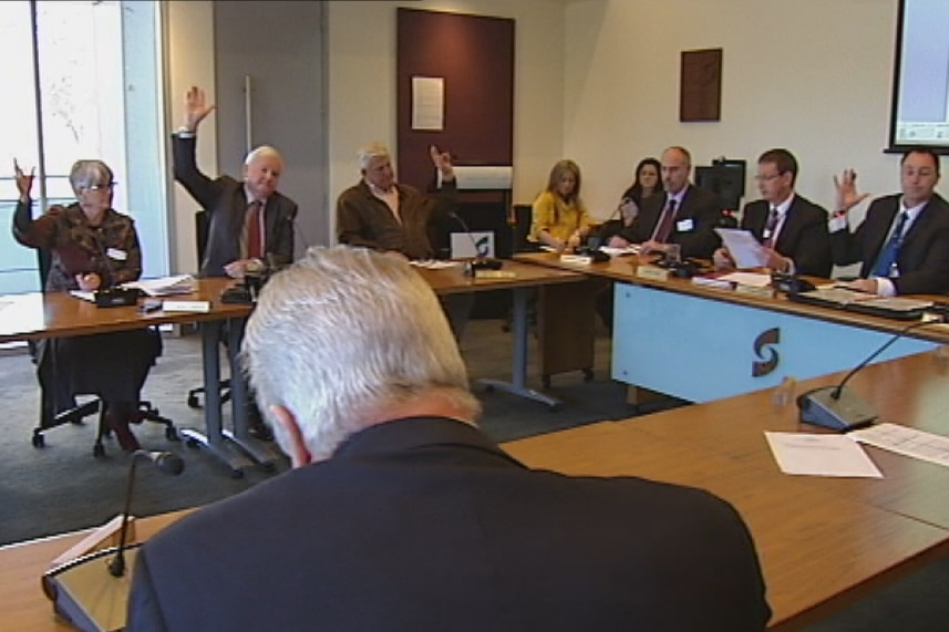 A group of people raise their hands at a table during a meeting
