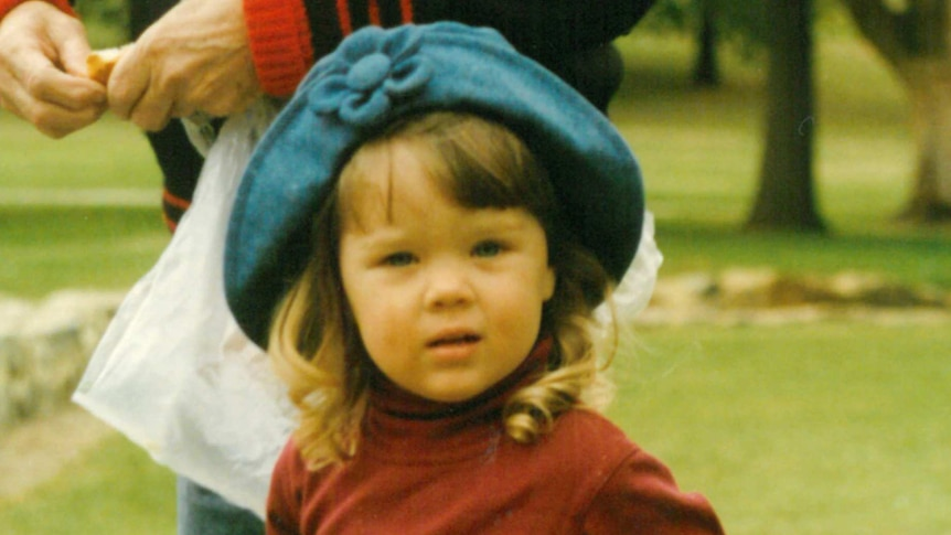 A toddler girl wearing a blue hat and jeans feeds ducks in a park.