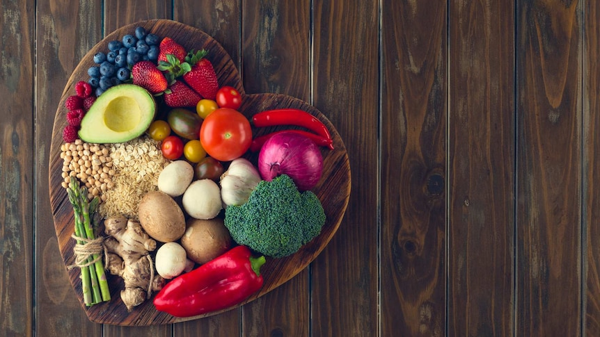 Fruits, vegetables and grains stacked on a chopping board shaped like a heart