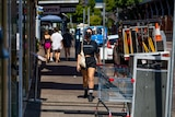 A woman wears a face mask while walking in Darwin CBD. She is wearing black shorts and a black top. It is a sunny day.