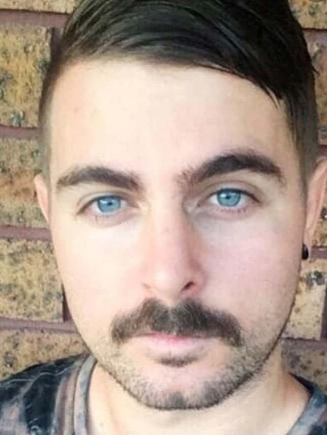 Man with cropped hair and blue eyes.