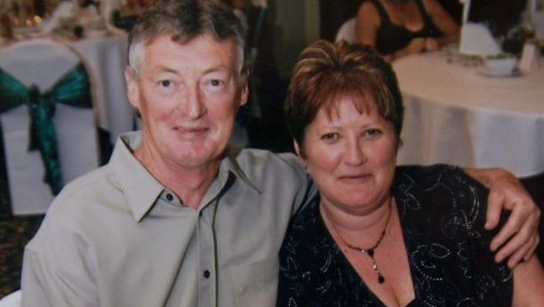 A man and woman smile at the camera.