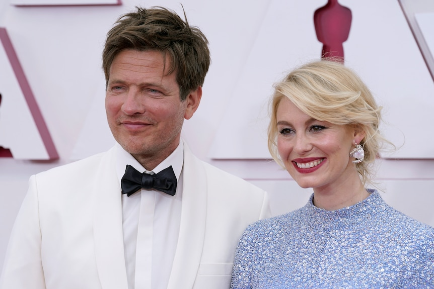 A man in a white tuxedo with a black bow tie, and a woman in a light blue sparkly dress.