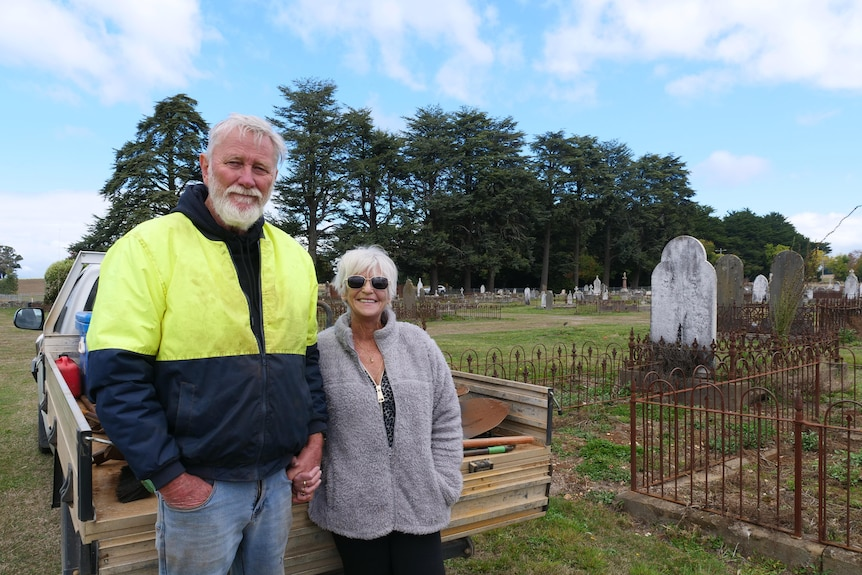 man and woman in their sixties standing and smiling in a graveyard.