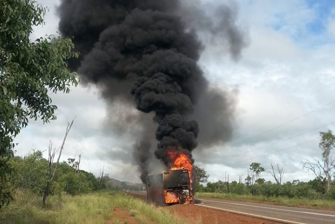 Thick black smoke rises into the sky from a burning school bus on the side of a regional highway.