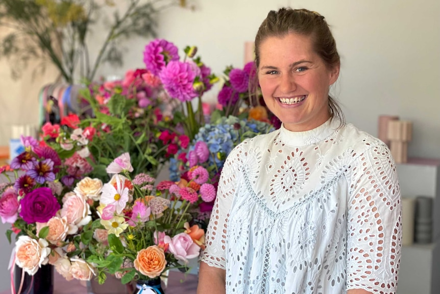 A woman in a white shirt smiles at the camera in front of a number of bunches of flowers