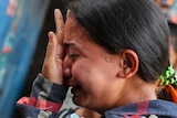 A close up photo shows a crying woman pressing her open left palm on her nose.