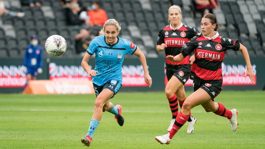 Mackenzie Hawkesby in the blue kit of Sydney FC is chased by Olivia Price in the red and horizontal black stripes of WSW