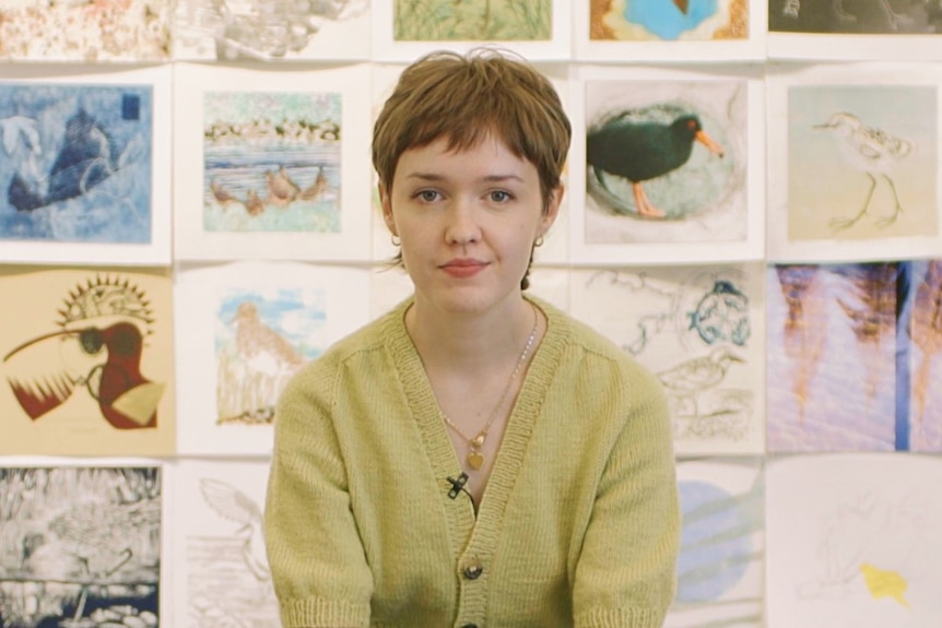 Mary McGillivray, a young woman with a short haircut, sitting in front of a wall of drawings at a gallery