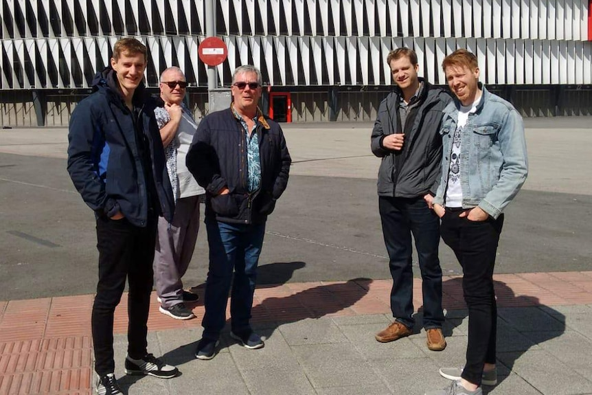 Alan Dennison stands outside with four other men.