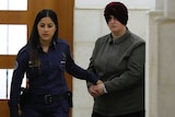 Malka Leifer is led from the court by a police woman.
