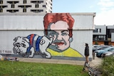 A mural in Footscray showing a bulldog cock his leg ove a depiction of Pauline Hanson's face.