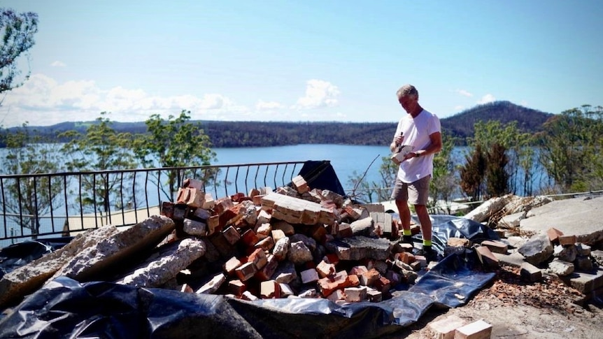 A man stands on a pile bricks while using a tool to clean one of the bricks. Behind him is a view of Lake Conjola.