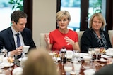 Julie Bishop speaks at a table covered in food and tea.