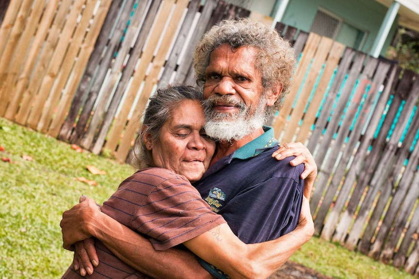 An older man and woman embracing.