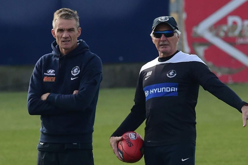 An AFL assistant coach stands with arms folded, while the senior coach holds a football at training.