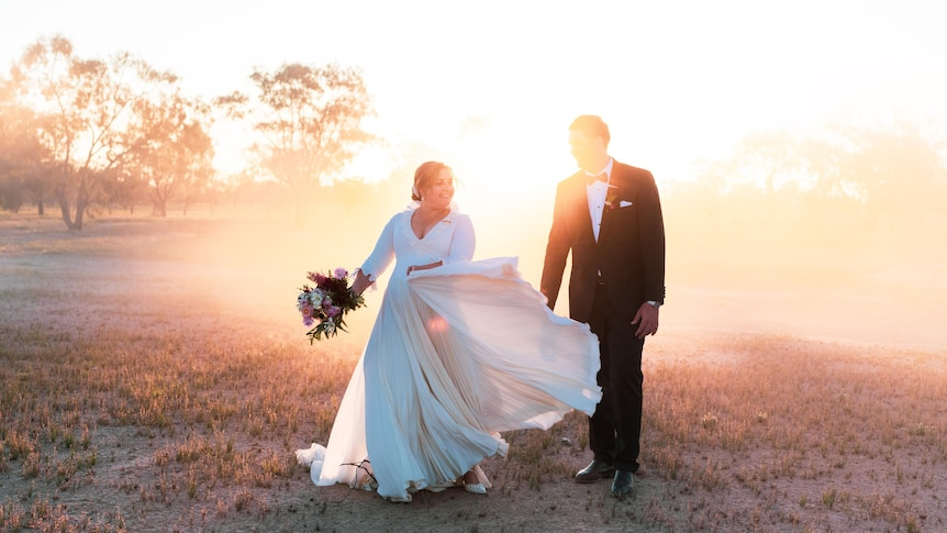 A bride and groom smile at each other in dusty setting
