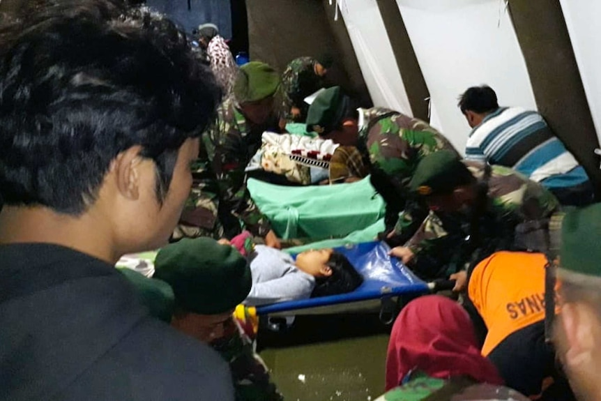 Indonesian soldiers tend to a woman injured in the earthquake at a makeshift hospital