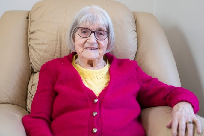 An elderly woman in a red cardigan sits smiling in a lounge chair