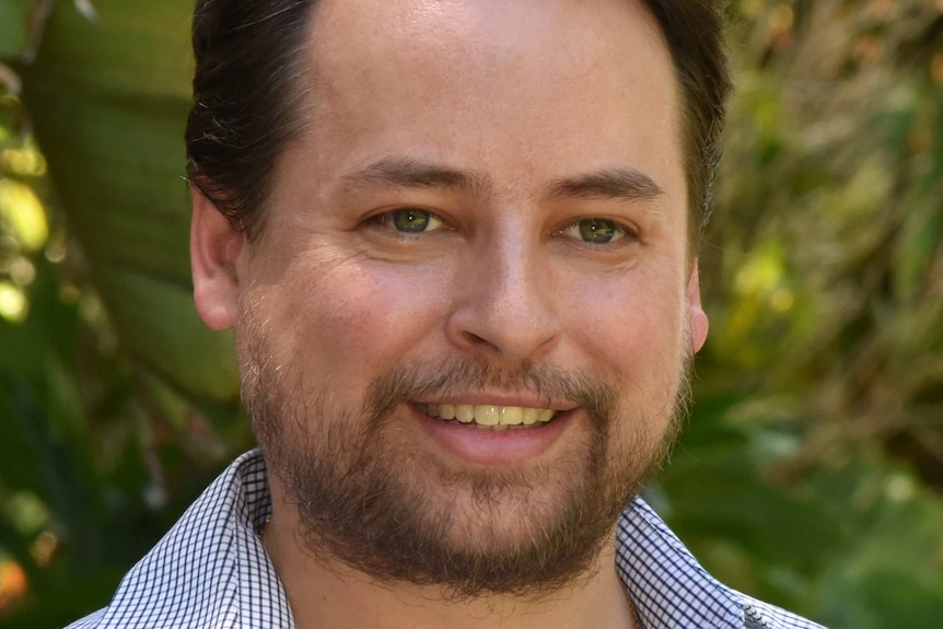 A man with brown hair smiles. He is wearing a blue and white cheque shirt with a collar. He has facial hair.