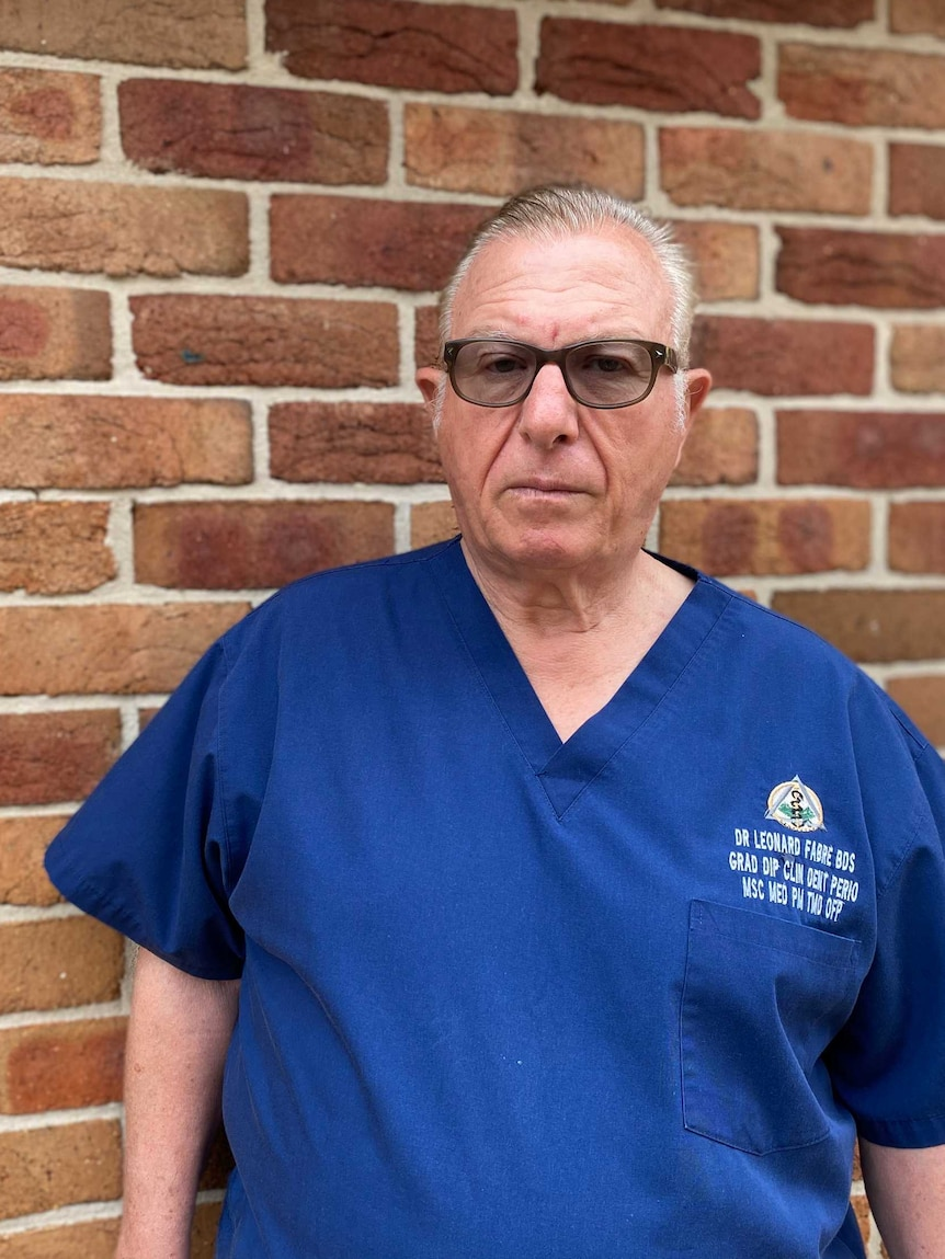 A man in a blue dentist uniform and tinted glasses stands against a brick wall