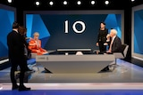 Theresa May wears and orange suit, which is adjusted by on-set assistants as jeremy paxman sits across from her sipping a coffee