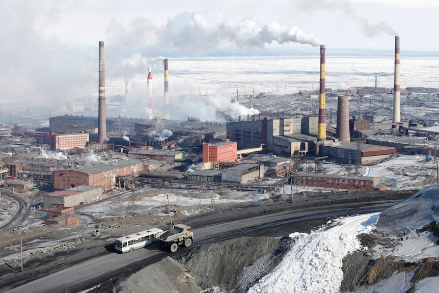 Smoke rises from chimneys of Norilsk Nickel's nickel plant which is pictured surrounded by snow.