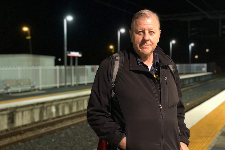 A man standing with black jacket, looking like he has come back from work, at night at the train station.
