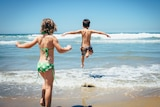 Two kids leap into the surf on a sunny day.